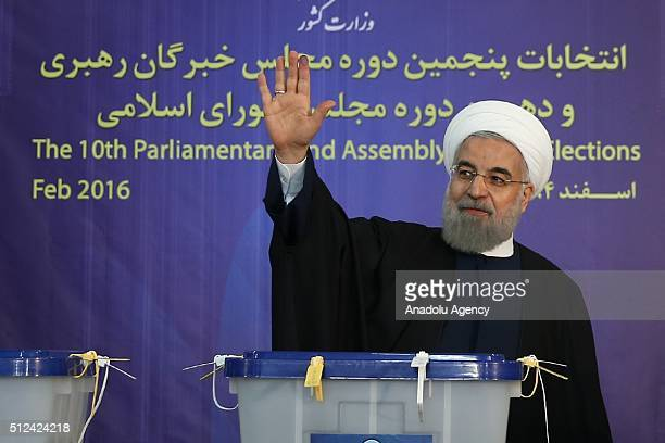Iranian President Hassan Rouhani greets people after casting his ballot for both parliamentary and the Assembly of Experts elections at a polling...