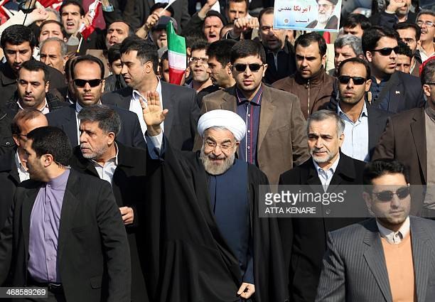 Iranian President Hassan Rouhani greets supporters prior to giving a speech during a rally in Tehran's Azadi Square to mark the 35th anniversary of...