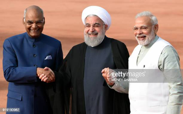 Iranian President Hassan Rouhani holds hands with Indian President Ram Nath Kovind and Indian Prime Minister Narendra Modi during a ceremonial...