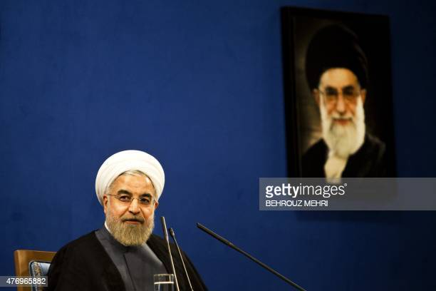 Iranian President Hassan Rouhani listens sitting next to a portrait of supreme leader Ayatollah Ali Khamenei during a press conference in Tehran on...