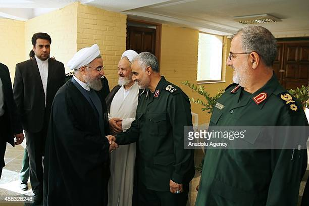 Iranian President Hassan Rouhani shakes hands with Iranian Quds Force commander Qassem Soleimani as Revolutionary Guards' ground forces commander...