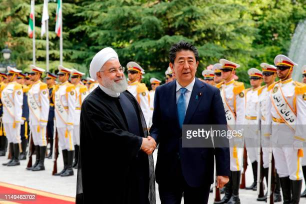 Iranian President Hassan Rouhani shakes hands with Japanese Prime Minister Shinzo Abe during a welcoming ceremony at the Saadabad Palace in the...