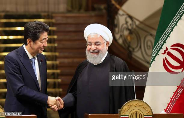 Iranian President Hassan Rouhani shakes hands with Japanese Prime Minister Shinzo Abe at the Saadabad Palace in the capital Tehran on June 12 2019...
