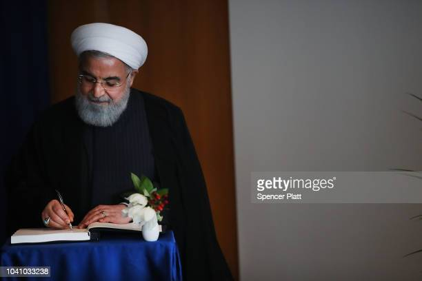 Iranian President Hassan Rouhani signs a book as he attends a meeting with Antonio Guterres the SecretaryGeneral of the United Nations during the...