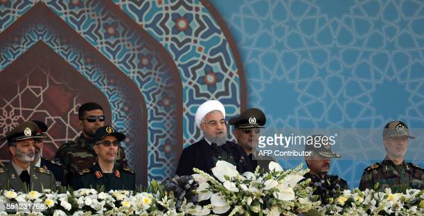 Iranian President Hassan Rouhani sits among senior army staff as he delivers his speech during the annual military parade marking the anniversary of...