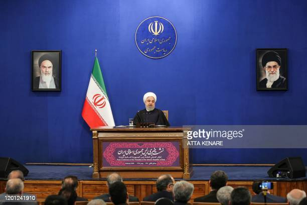 Iranian President Hassan Rouhani speaks during a news conference in the capital Tehran, on February 16 with the portraits of Iran's former and...