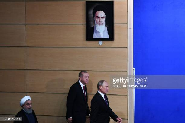 Iranian President Hassan Rouhani Turkish President Recep Tayyip Erdogan and Russian President Vladimir Putin walks past a portrait of founder of the...