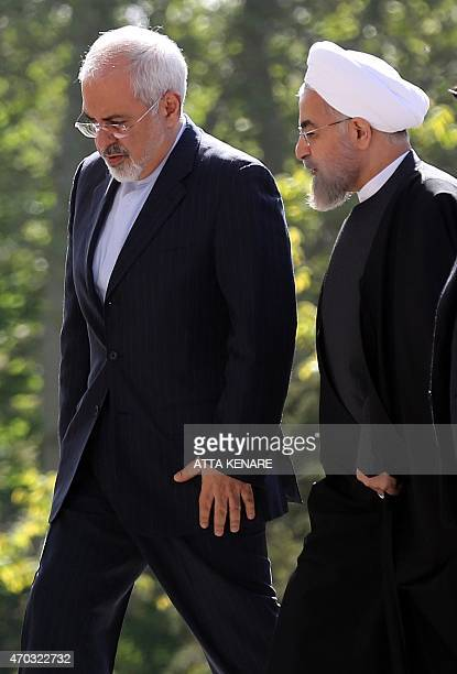 Iranian President Hassan Rouhani walks next to his Foreign Minister Mohammad Javad Zarif as they arrive for a welcome ceremony for Afghan President...