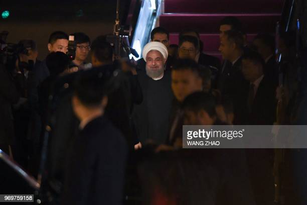 Iranian President Hassan Rouhani walks out from the airplane upon his arrival at Qingdao Liuting International Airport in Qingdao China's Shandong...