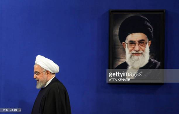Iranian President Hassan Rouhani walks past a portrait of Supreme Leader Ayatollah Ali Khamenei as he arrives for a news conference in the capital...