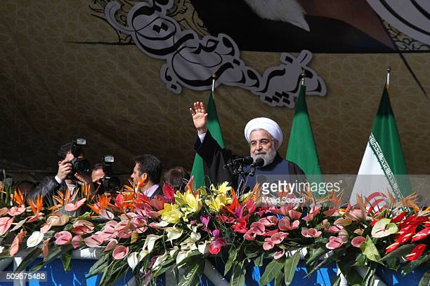Iranian President Hassan Rouhani waves to the crowd during a rally to mark the 37th anniversary of the Islamic revolution in Azadi Square on February...