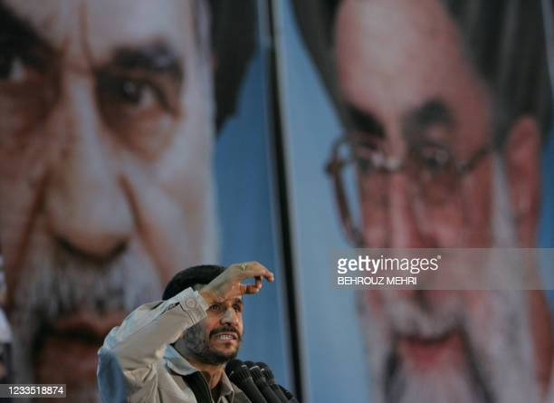 Iranian President Mahmoud Ahmadinejad gestures as he delivers a speech in front of portraits of Iran's late founder of the Islamic Republic Ayatollah...