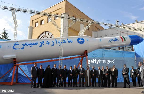 Iranian President Mahmoud Ahmadinejad poses with government officials underneath the Simorgh homebuilt satellite rocket during the unveiling ceremony...