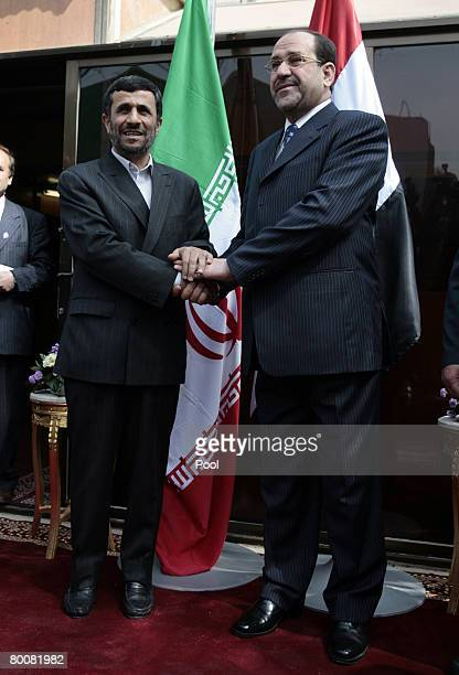 Iranian President Mahmoud Ahmadinejad shakes hands with Iraqi Prime Minister Nuri alMaliki at the latter's office in the heavily fortified Green Zone...