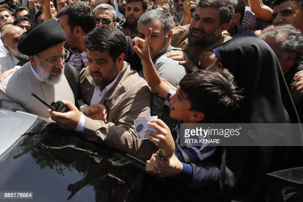 TOPSHOT Iranian presidential candidate Ebrahim Raisi greets supporters as he leaves after castiong his ballot for the presidential elections at a...
