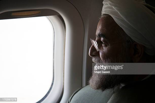 Iranian presidential candidate Hasan Rowhani a former Iranian nuclear negotiator looks on from inside an airplane during a campaign tour on June 12...