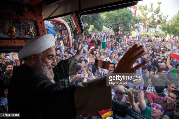 Iranian presidential candidate Hasan Rowhani a former Iranian nuclear negotiator waves to supporters during a campaign tour on June 12 2013 in...
