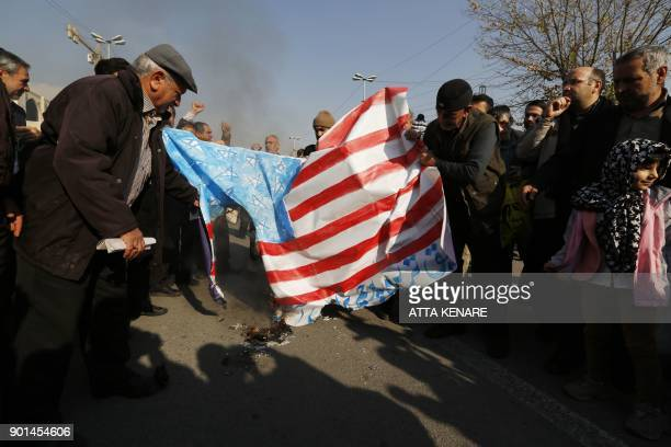Iranian progovernment demonstrators set a makeshift US flag on fire during a march after the weekly Muslim Friday prayers in Tehran on January 5 2018...