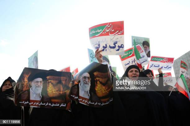 TOPSHOT Iranian progovernment supporters hold posters of Iran's supreme leader Ayatollah Ali Khamenei during a rally in support of the regime after...