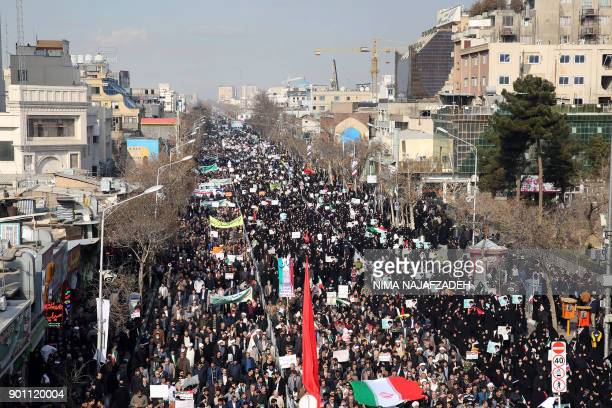 Iranian progovernment supporters march during a rally in support of the regime after authorities declared the end of deadly unrest in the city of...