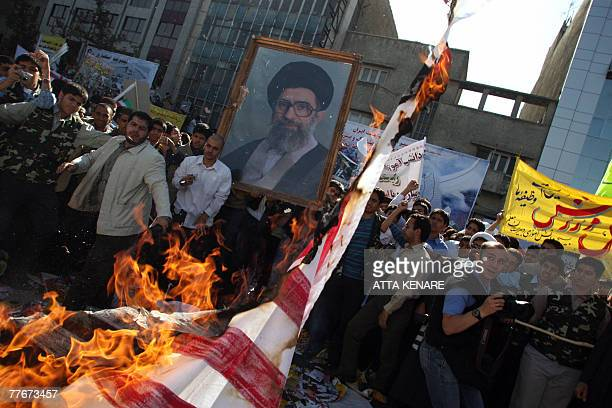 Iranian protesters burn a reproduction of a US flag whilst others hold up a large portrait of Iran's supreme leader Ayatollah Ali Khamenei during a...