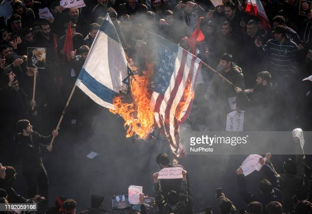Iranian protesters burn an Israel and the US flags while attending a mass funeral for the commander of the IRGS Qods Force Qasem Soleimani...