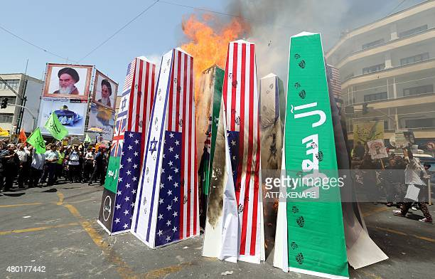 Iranian protesters burn Israeli US and Saudi Arabian flags during a demonstration to mark the Quds International day in Tehran on July 10 2015 AFP...