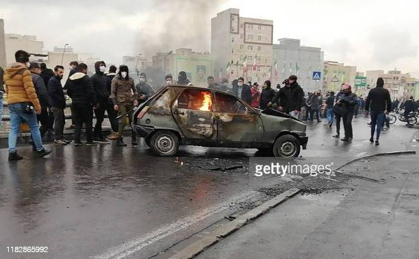 Iranian protesters gather around a burning car during a demonstration against an increase in gasoline prices in the capital Tehran on November 16...