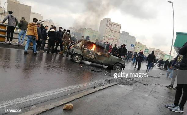Iranian protesters gather around a burning car during a demonstration against an increase in gasoline prices in the capital Tehran, on November 16,...