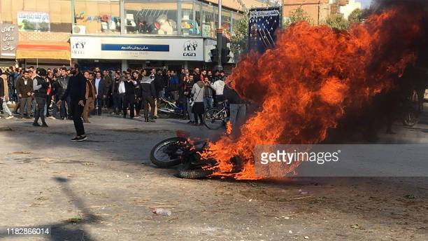 Iranian protesters gather around a burning motorcycle during a demonstration against an increase in gasoline prices in the central city of Isfahan,...