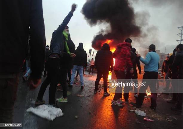 Iranian protesters gather around a fire during a demonstration against an increase in gasoline prices in the capital Tehran, on November 16, 2019. -...