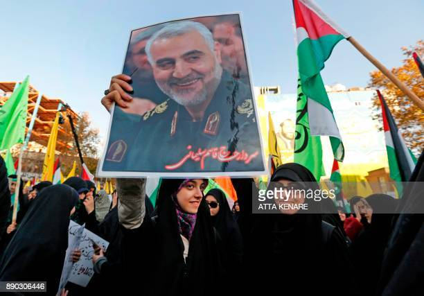 Iranian protesters hold a portrait of the commander of the Iranian Revolutionary Guard's Quds Force Gen Qassem Soleimani during a demonstration in...