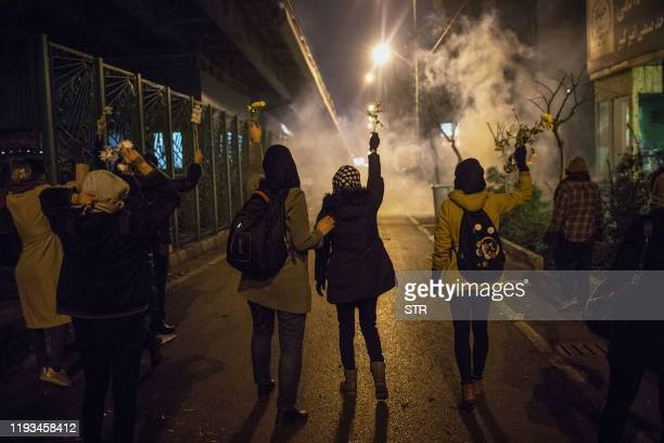 Iranian protesters hold flowers as riot police fire tear gas during a demonstration in front of Tehran's Amir Kabir University on January 11 2020...