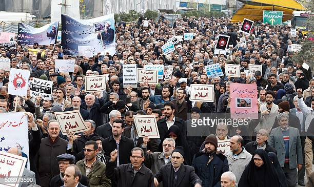 Iranian protesters hold placards and shout slogans during a demonstration in Tehran on January 8 against the execution of prominent Shiite Muslim...