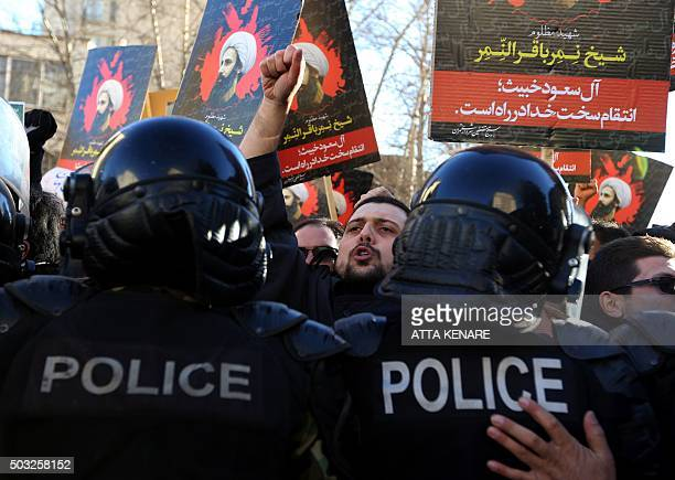Iranian protesters hold portraits of prominent Shiite Muslim cleric Nimr alNimr as they confront riot police during a demonstration against his...