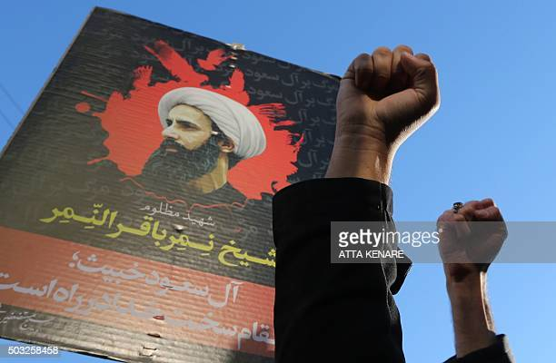 Iranian protesters raise their fists in front of a portrait of prominent Shiite Muslim cleric Nimr alNimr during a demonstration against his...