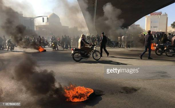 Iranian protesters rally amid burning tires during a demonstration against an increase in gasoline prices in the central city of Isfahan on November...