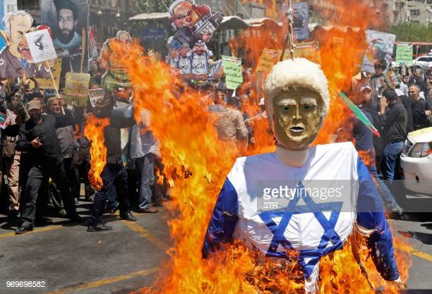 Iranian protestors burn an effigy of US President Donald Trump dressed in an Israeli flag during a rally to mark Qods day an annual day of...