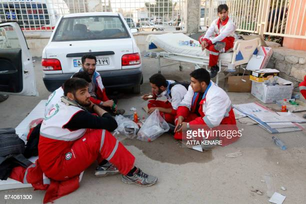 Iranian Red Crescent paramedics eat and rest during a break from tending to quake victims and survivors in the town of Sarpole Zahab in the western...