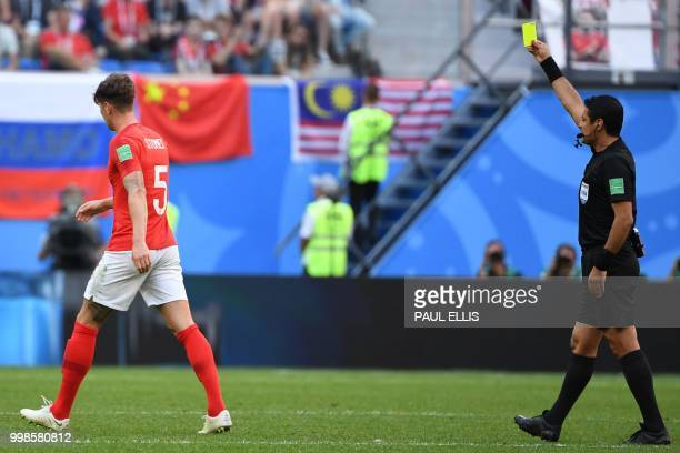 Iranian referee Alireza Faghani gives a yellow card to England's defender John Stones during their Russia 2018 World Cup playoff for third place...