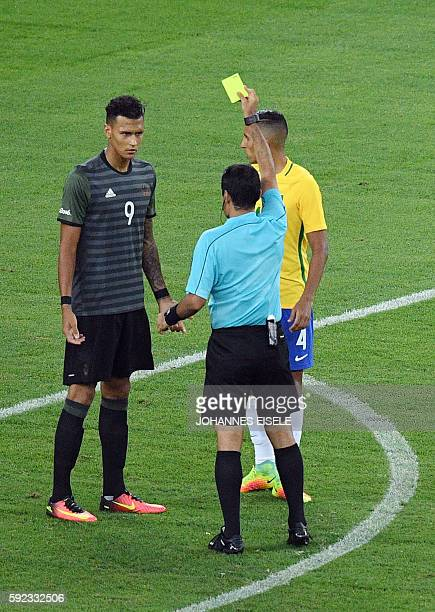 Iranian referee Alireza Faghani shows a yellow card to Germany's forward Davie Selke during the Rio 2016 Olympic Games men's football gold medal...