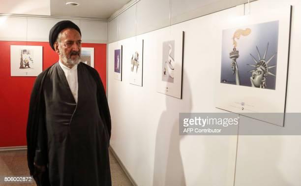 Iranian reformist cleric Mahmoud Doaei looks at cartoons of US President Donald J Trump at an exhibition of the Islamic Republic's 2017 International...