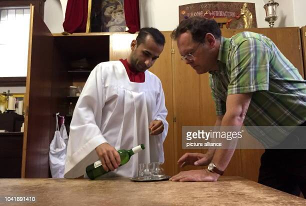Iranian refugee Milad Ramezanpour stands next to vicar Andreas Muller in the in the vestry of the Caltholic church of St Anton and serves altar wine...