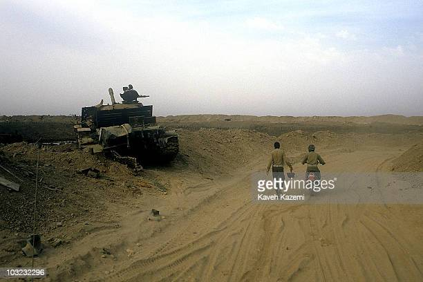 Iranian Revolutionary Guards pass a destroyed Iraqi tank in AlFao Peninsula Iraq 15th February 1986 The Iranians launched a surprise attack against...