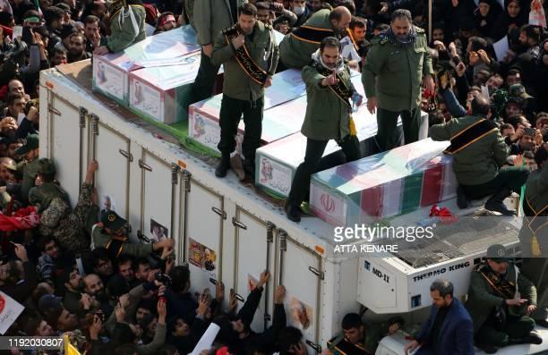Iranian revolutionary guards surround the coffins of slain Iranian military commander Qasem Soleimani Iraqi paramilitary chief Abu Mahdi alMuhandis...
