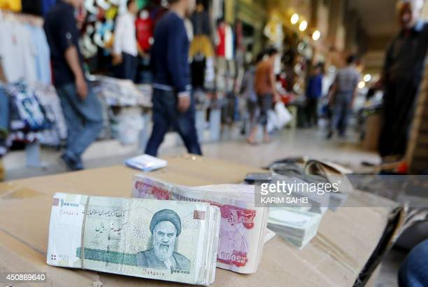 Iranian rial banknotes bearing a portrait of the late founder of the Islamic Republic of Iran Ayatollah Ruhollah Khomeini sit on the stand of an...
