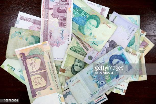 Iranian rials are displayed in Tehran on July 31, 2019. - The government in sanctions-hit Iran on Wednesday approved a plan to remove zeros from the...