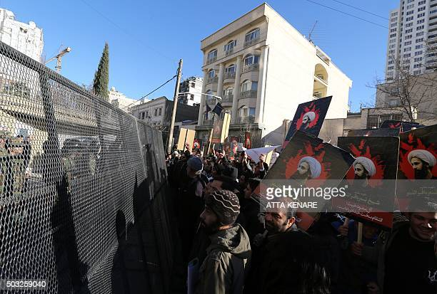 Iranian riot police block a street leading to the Saudi embassy as protesters hold portraits of prominent Shiite Muslim cleric Nimr alNimr during a...