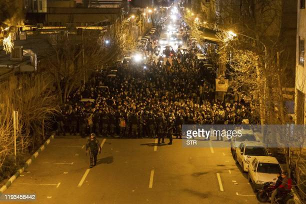 Iranian riot police stand guard as protesters gather in front of Tehran's Amir Kabir University on January 11, 2020. - Demonstrations broke out for a...