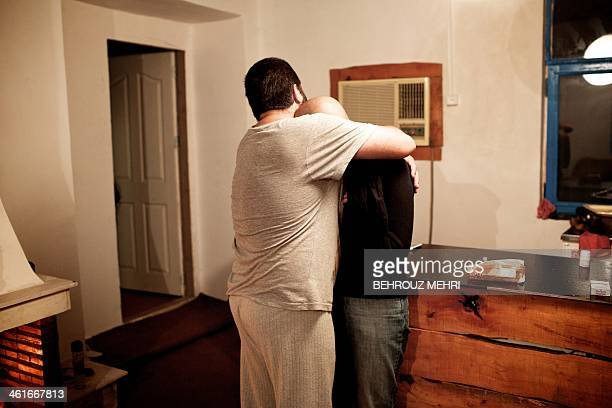 Iranian Saleh hugs her fiance a breast cancer patient Farvah in their countryside house in a village near the Caspian Sea port city of Bandar Anzali...